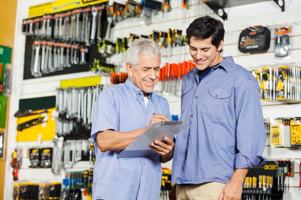 Smiling father and son checking checklist on clipboard while standing in hardware store